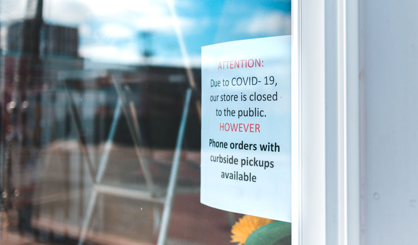 Store offering curbside pickup sign on door