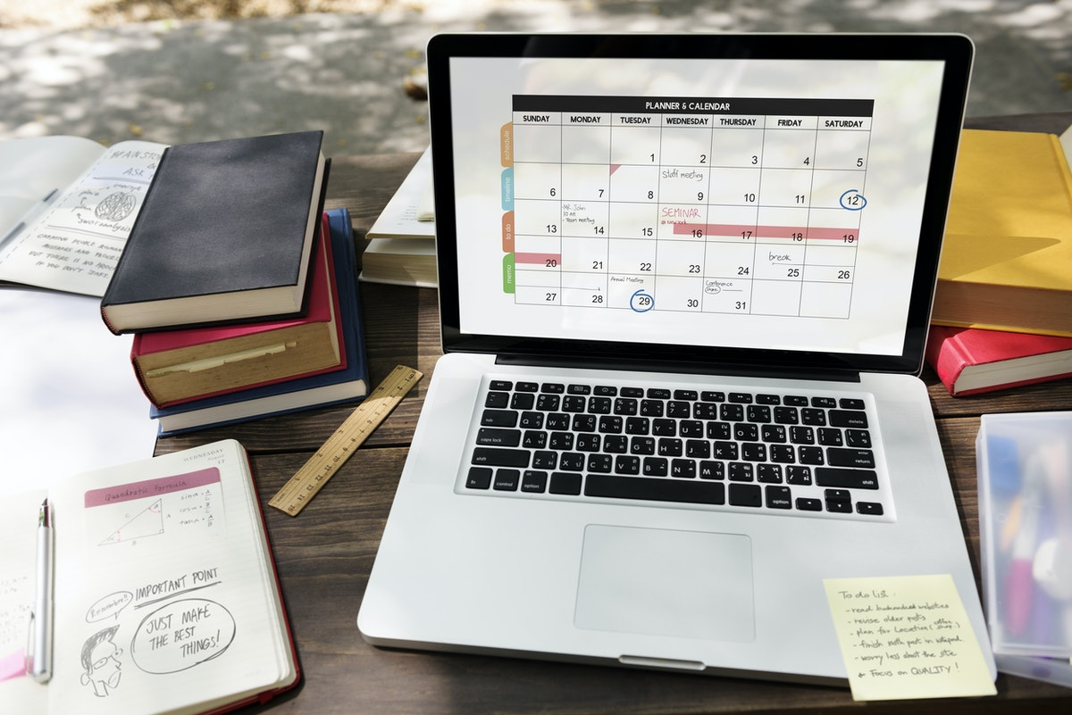 laptop with calendar app open sitting on table with books and papers